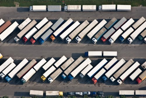 an overhead view of a large car park filled with cargo lorries