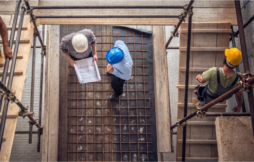 an over head view of work men discussing plans on a building site